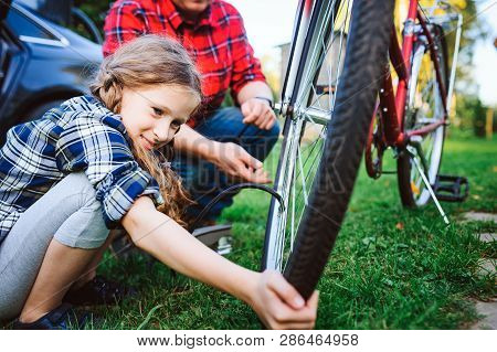 Father And Daughter Fixing Problems With Bicycle Outdoor In Summer. Kid Girl Spending Time Together