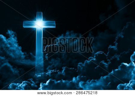 Concept Of Christian Religion Shining Cross On The Background Of Cloudy Night Sky. Dark Sky With Cro