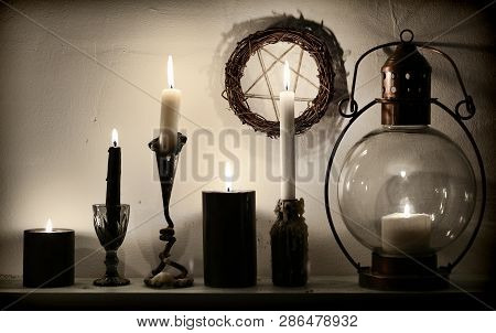 Vintage lamp, weird candles and pentagram on the wall. Magic gothic ritual. Wicca, esoteric, divination and occult background with vintage objects poster