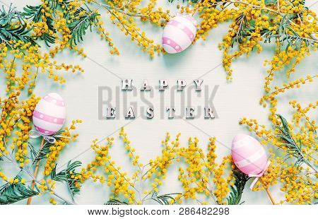 Easter background. Easter eggs , mimosa flowers and festive inscription Happy Easter - holiday Easter card