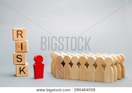 Wooden Blocks With The Word Risk And A Team With A Leader. Business Concept Of Teamwork, Crisis Solu