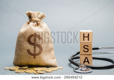 Wooden Blocks With The Word Hsa And Money Bag With Stethoscope. Health Savings Account. Health Care.