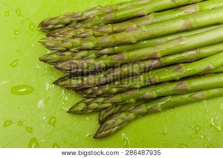 Top View Of Fresh Green Asparagus On Green Background