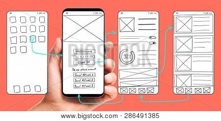 UI development. Male hand holding smartphone with wireframed user interface screen prototypes of a mobile application on living coral background.