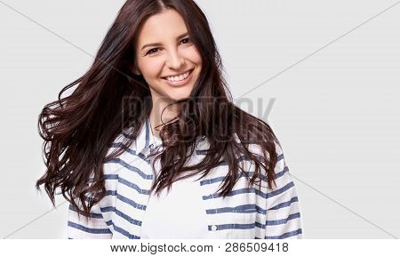 Closeup Indoor Portrait Of Beautiful Brunette Young Woman With Long Hair Smiling Cheerfully. Charmin