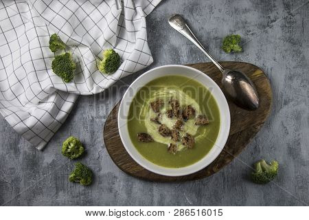 Top View Of Served Brocoli Creamy Soup With Cream And Bread Croutons On Rustic Table With Spoon And
