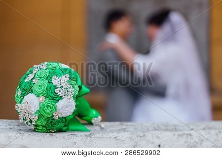 Handmade Ribbon Wedding Bouquete And Inloved Couple On The Background.