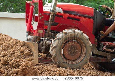 Worker Driving The Tractor For Grading The Level Of Ground