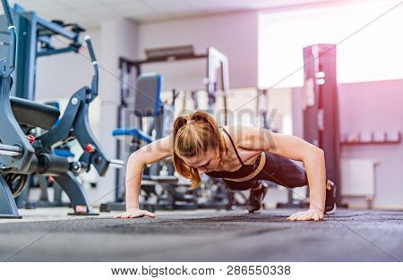 Strong Young Woman Doing Push-ups In Gym. Young Woman With Muscular Body. Fitness Concept.
