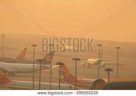 An Airplane Landing At Dusk.