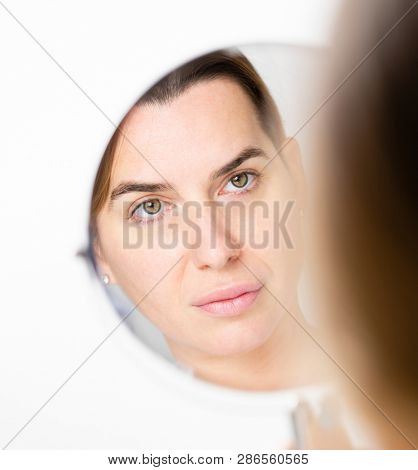 Beautiful middle aged woman in mirror reflection. Skin care