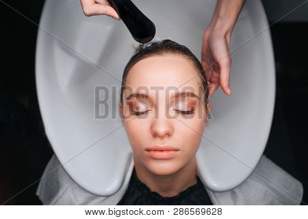 Top View Of Beautiful Young Woman With Closed Eyes Sitting On White Hair Wash Sink While Hairdresser