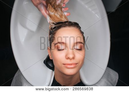 Top View Of Beautiful Young Woman With Closed Eyes Smiling While Hairdresser Washing Blonde Hair. Ha