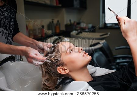 Beautiful Young Woman Looking At Phone While Hairdresser Washing Her Hair After Mask In Beauty Salon