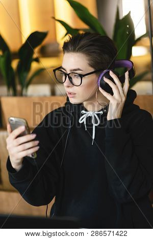 Shortcut Hipster Girl Wearing Glasses Activate The Music On Her Smartphone While Sitting At The Tabl