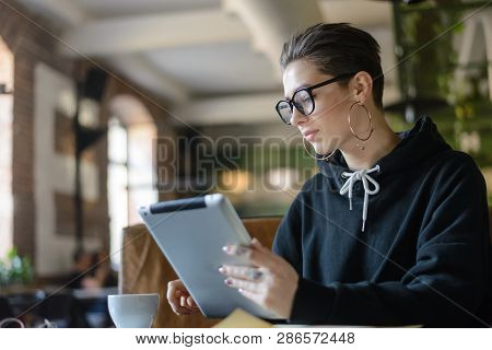 Dreamy Attractive Shortcut Student In Stylish Optical Spectacles Sitting At Wooden Table In Cafeteri