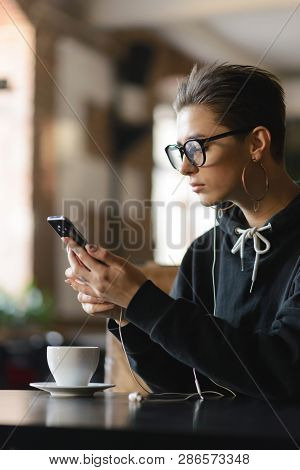 Shortcut Hipster Girl Wearing Glasses Listening Music In Headphones Connected To Smartphone