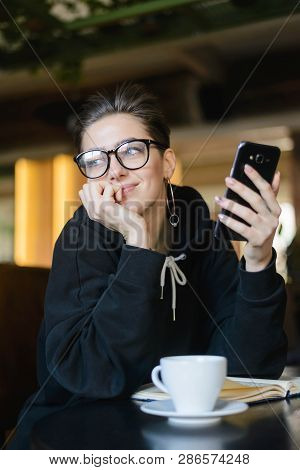 Shortcut Hipster Young Blogger Sitting With Smartphone At The Wooden Table And Looking To The Window
