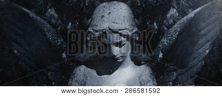 Angel Of Death. Retro Styled Ancient Statue Of Sad Angel As Symbol Of Pain, Fear And End Of Life.