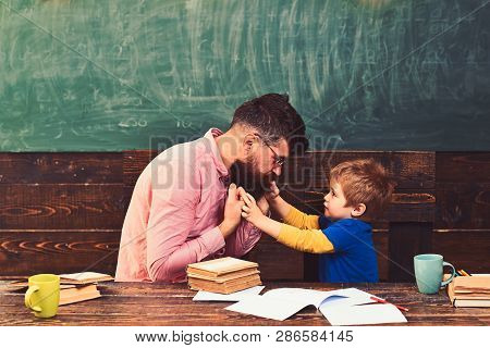 Male Teacher Giving Explanations To Small Kid. Tutor And His Little Student Have Conversation About