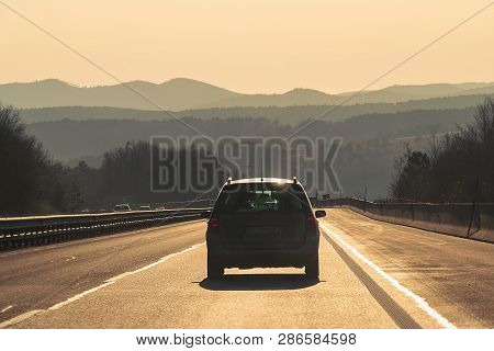 poster of Car travel in highway. Traveling by car on the road. Car in highway landscape in sunset. Travel by car in the highway in sunset landscape. Car. Travel. Landscape. Sunset. Road trip.