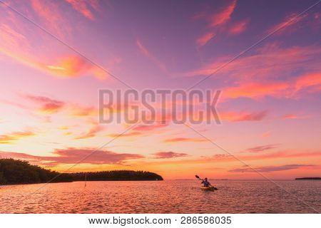 Kayaker man kayaking sea kayak at sunset on summer ocean nature landscape. Amazing scenery with pink colored sky.