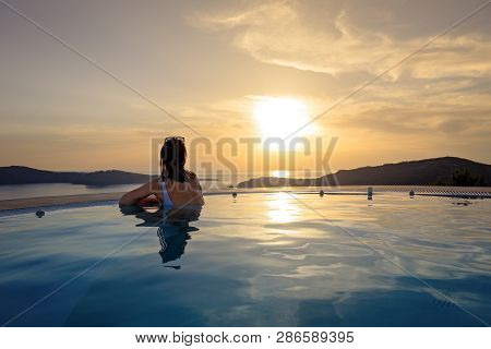 Woman In Infinity Swimming Pool At Golden Sunset. Girl Admiring Sunset From The Pool. Summer Vacatio
