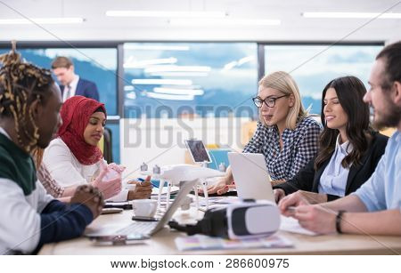 multiethnic startup business team discussing new business plan,working on laptop and tablet computer while learning about drone technology for new business advancement