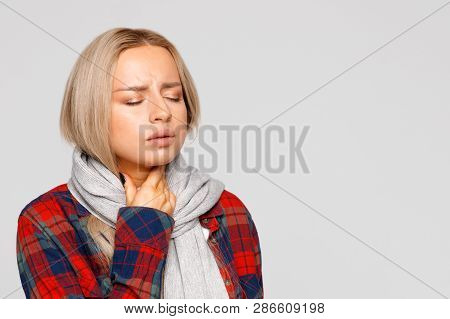 Portrait Of Upset Young Woman In Checked Shirt, Wrapped Scarf  Having Sore Throat, Holding Hand On H