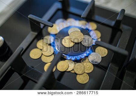 Cost Of Gas, Concept Crisis. Gas Stove With Coins In Flame. The Cost Of Methane. Gas Coins More Expe