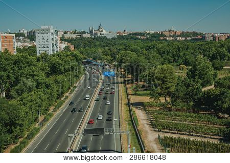 Multi-lane Highway With Heavy Traffic In The Midst Of Garden Trees And Apartment Buildings, In A Sun