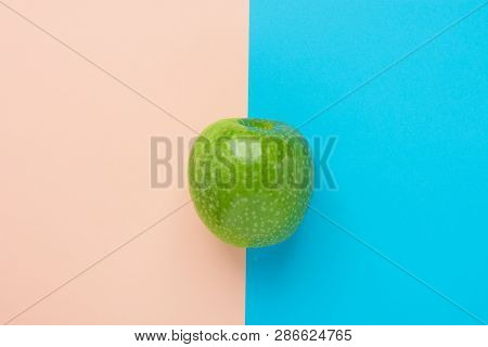 Green Organic Apple On Duotone Peachy Pink Mint Blue Background. Vitamins Healthy Diet Summer Detox