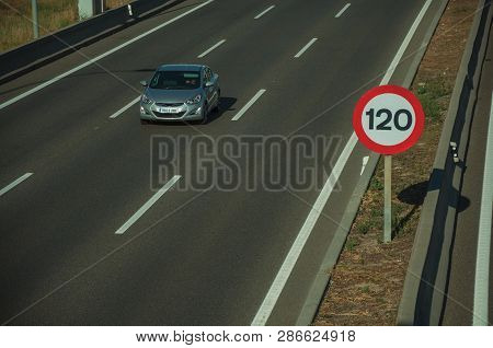 Cars Passing Through Multi Lane Highway And Speed Limit Signpost, On Sunset In Madrid. Capital Of Sp