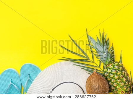 Ripe Pineapple Coconut On Green Palm Leaf White Straw Hat Blue Slippers On Bright Yellow Solid Backg