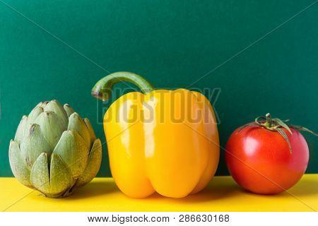 Ripe Organic Vegetables Artichoke Capsicum Tomato On Duotone Dark Green Yellow Background. Healthy P