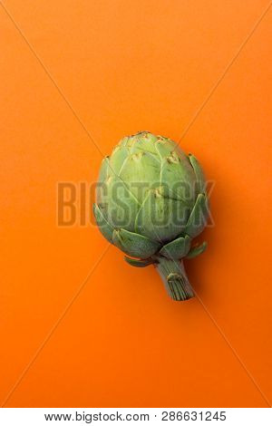 Ripe Green Artichoke On Solid Orange Background. Creative Food Poster. Minimalist Style. Mediterrane