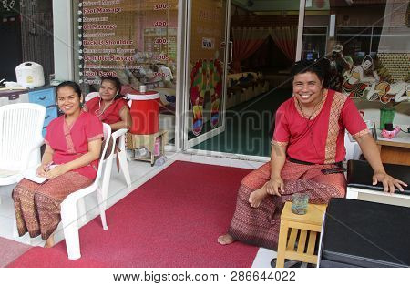 Karon Village, Phuket, Thailand - February 25, 2019: Unidentified Thai Masseurs Seat In Front Of The