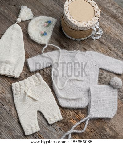 knitted newborn baby clothes composed on the wooden table