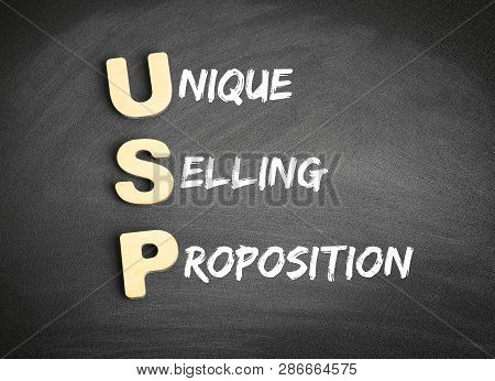 Wooden Alphabets Building The Word Usp - Unique Selling Proposition Acronym On Blackboard