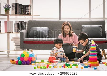 Asian Family, Leisure Time At Home, Young Beautiful Mother, Relaxing, Using Tablet On Couch, Two Kid