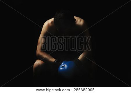 A Man In Boxing Gloves Is Sitting On A Chair In The Corner Of The Ring Against A Dark Background. Bo
