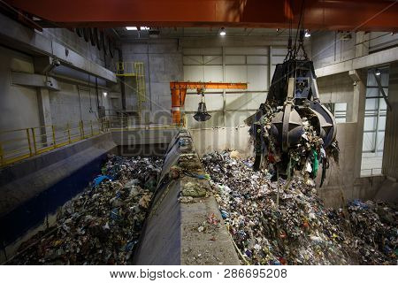 Mechanical Claw Hand Grabbing Pile Of Mixed Waste, Deposited In The Waste Treatment Plant Depot, Pre