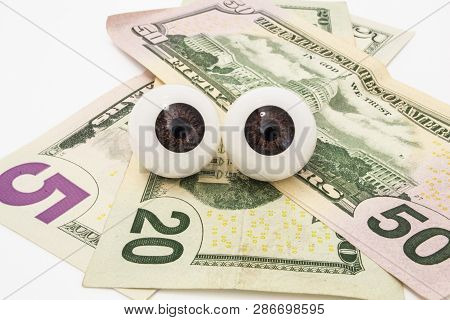 Pair Of The Eyes (eyeballs) Lie On Money (dollars) And Look At Object. Money Is Tracking You, Watch