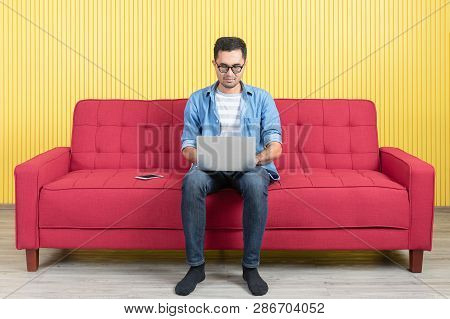 Young Asian Handsome Bearded Man, Wearing Eyeglasses In Denim Shirt, Comfortable Sitting On Red Sofa