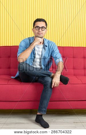 Young Asian Handsome Bearded Man, Wearing Eyeglasses In Denim Shirt, Sitting On Red Sofa, Resting On