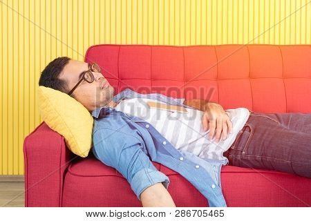 Young Asian Handsome Bearded Man Sprawled Out On Red Sofa In Modern Living Room, Bright Yellow Strip