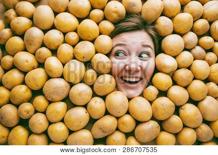 Woman With Potatoes, Concept For Food Industry. Face Of Laughing Woman In Potato Plane.