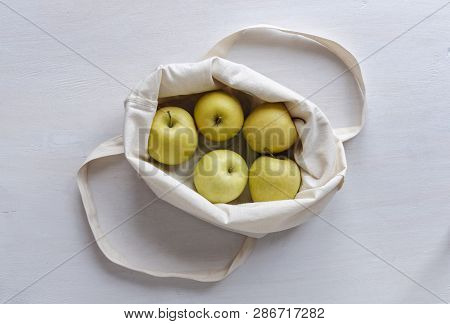 Cloth Shopping Bag With Fresh Healthy Golden Apples Folded Open To Reveal The Fruit Viewed Top Down