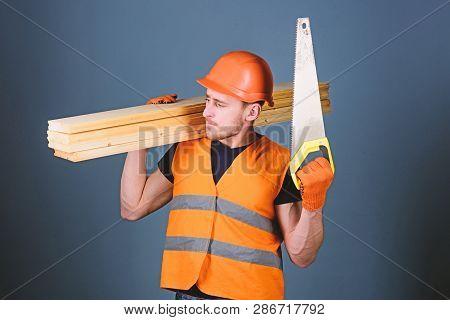 Woodcraft Concept. Man, Handyman In Helmet, Hard Hat Holds Handsaw And Wooden Beams, Grey Background
