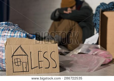 Selective Focus Of Homeless Man Holding Head On Knees While Sitting On Rubbish Dump With Cardboard C